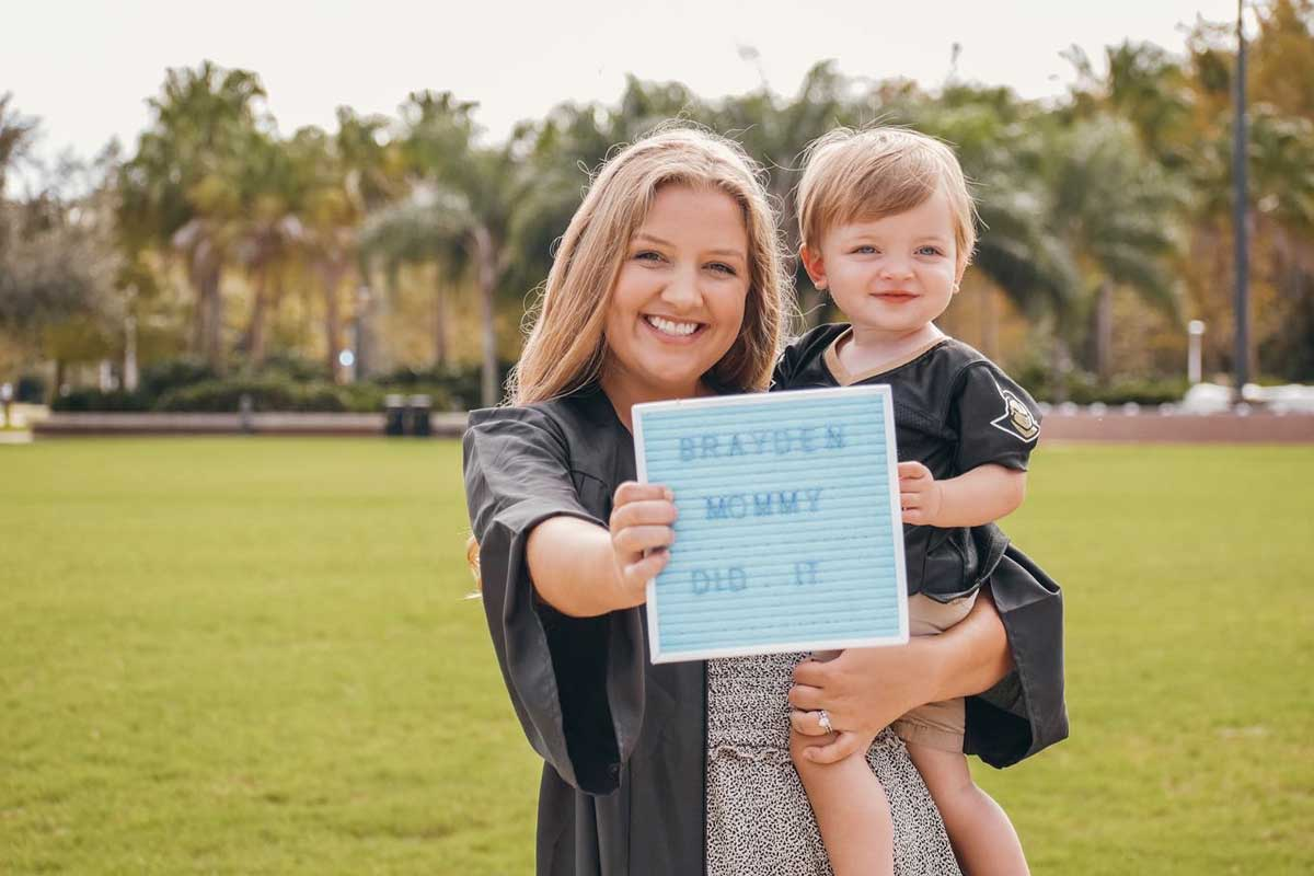 """Lindsey Palm holds her son and a sign that reads """"Brayden's mommy did it"""""""