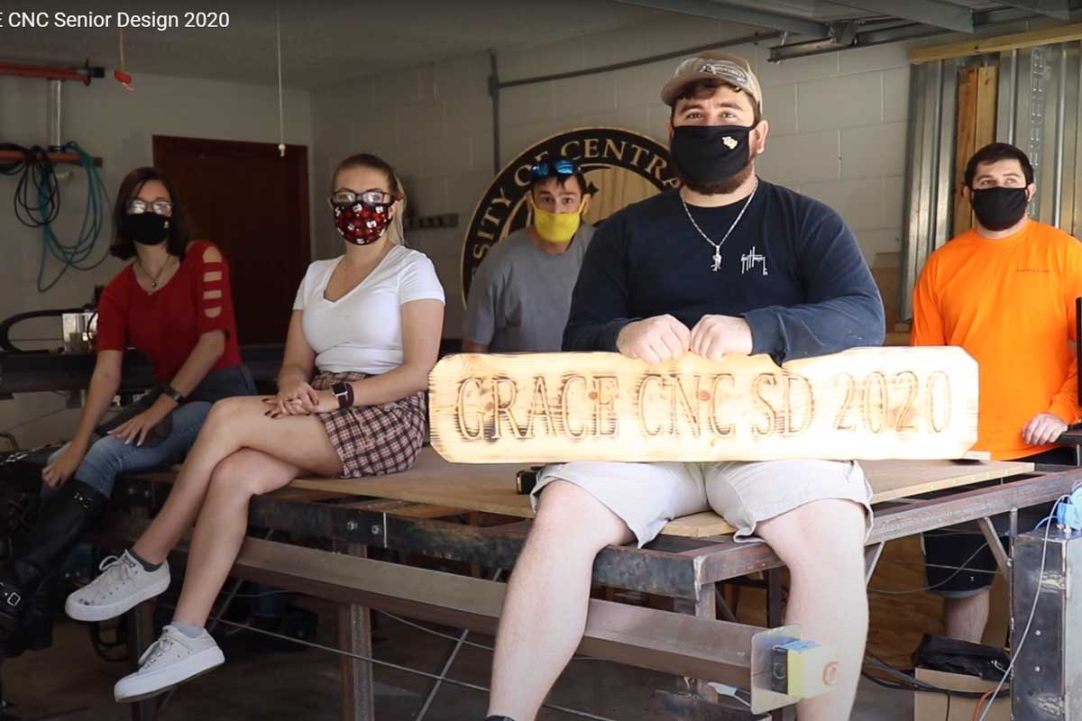 Zoom snapshot of 5 engineering students wearing masks in a workspace