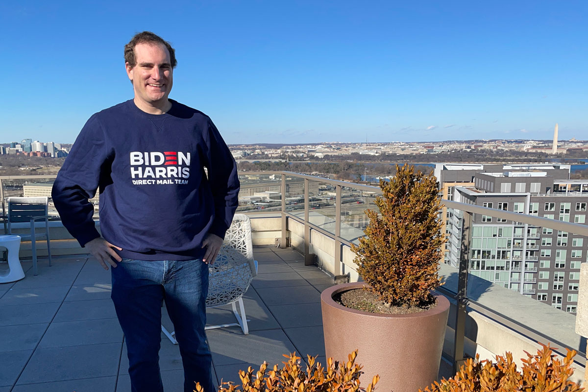 David Mariutto wears a Biden Harris sweatshirt and poses with the Washington Monument in the background