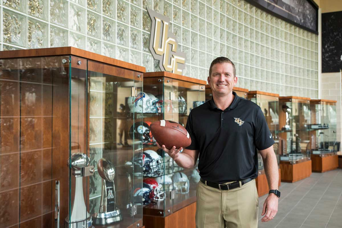 Danny White holds football in front of trophy cases