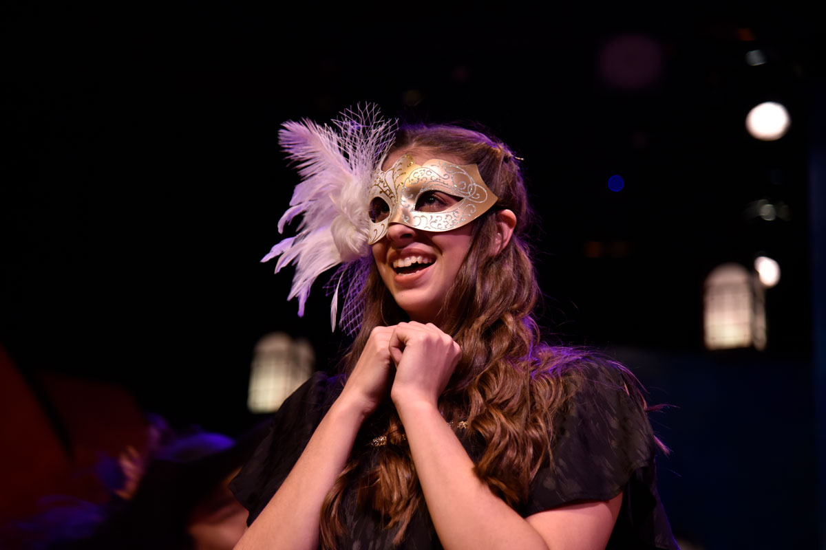 Woman in costume wearing gold mask with feather around the eyes smiles with hands under her chin