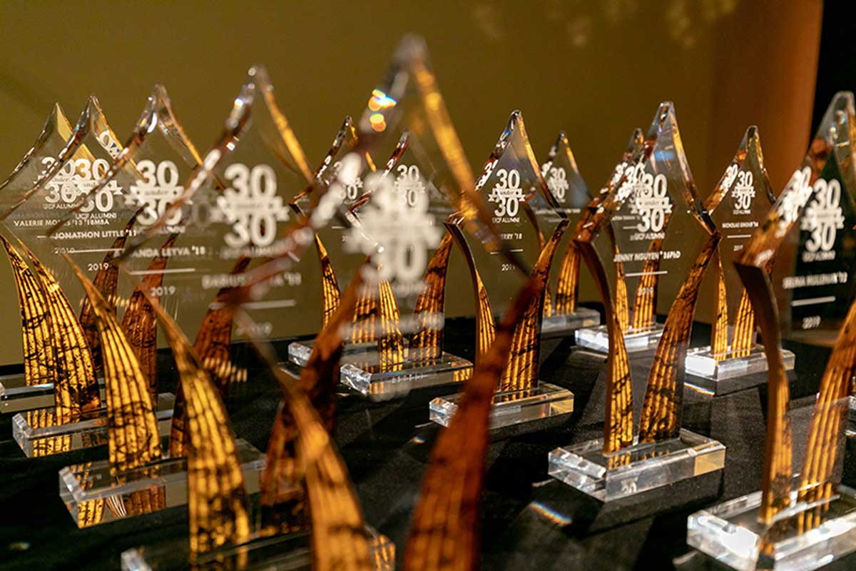 Glass awards in the shape of diamonds are in front of a yellow background. The awards say 30 Under 30 in white text.