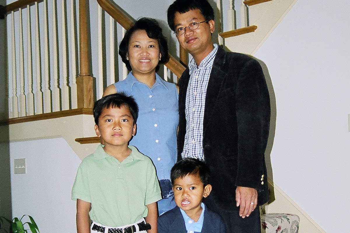 Mother and Father stand behind their two sons near a staircase