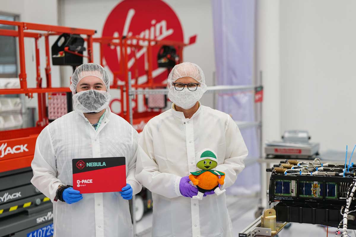 Two men in lab coats and masks stand next to each other, one holds a stuffed animal Citronaut and the other holds a red and black sign that says Nebula