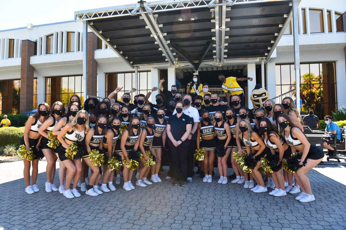 President Cartwright and First Lady Melinda pose with the cheerleading team