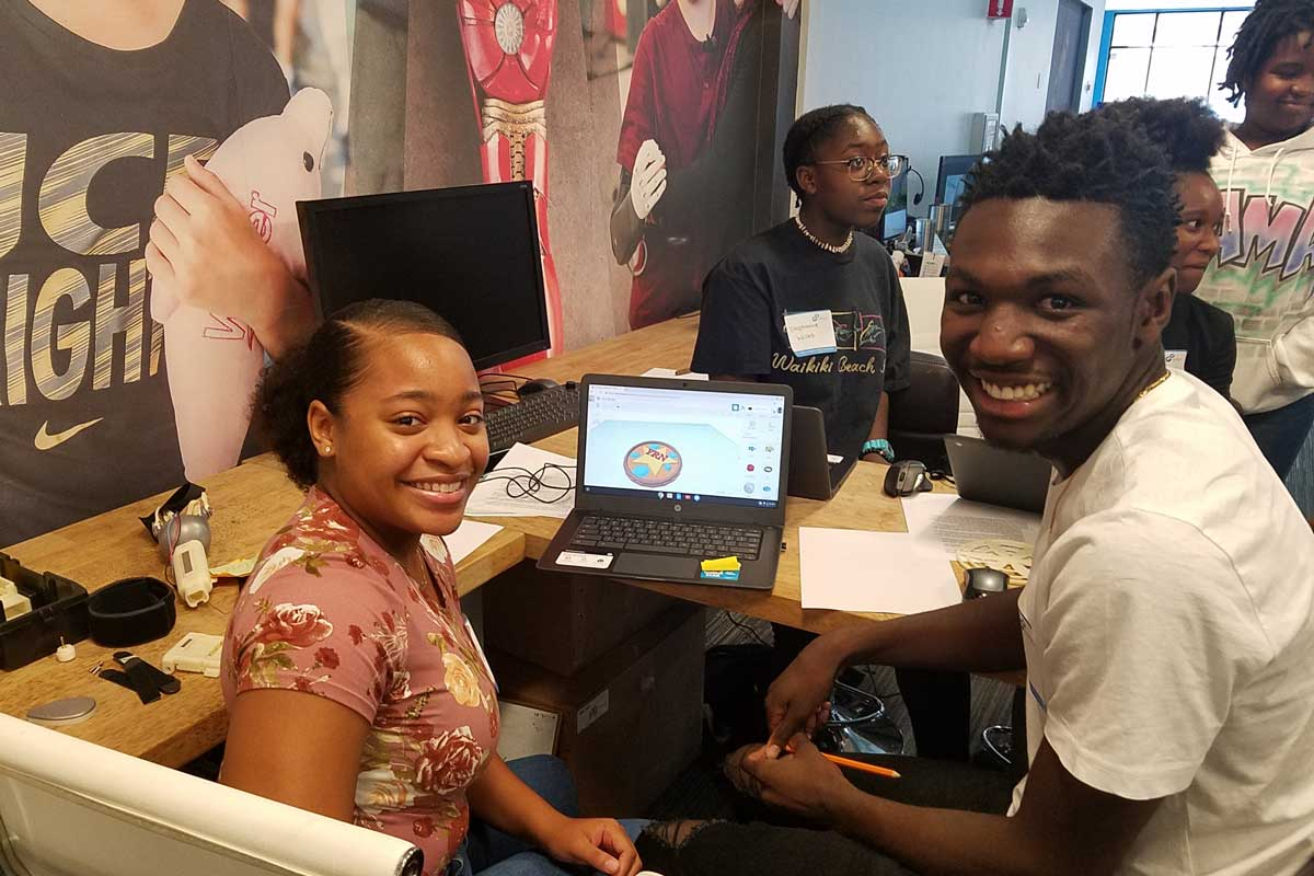 Students sit next to a computer and smile