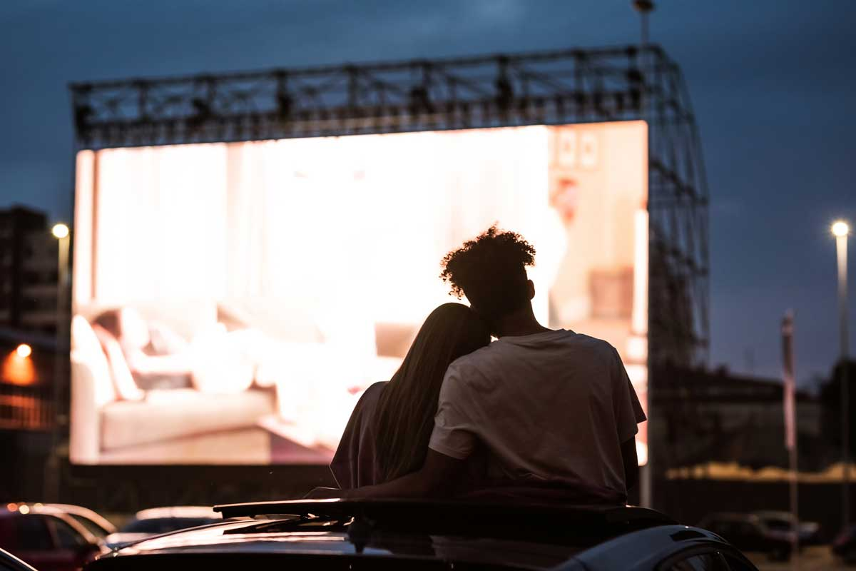 Silhouetted view of attractive young couple, boy and girl embracing, spending time together, sitting in the car while watching a movie in a drive in cinema.