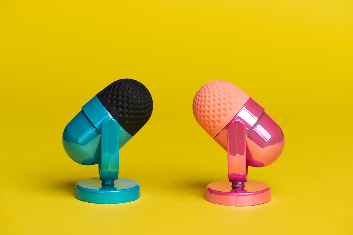 Two microphones facing each other. One microphone is pink the other microphone is blue on yellow background.