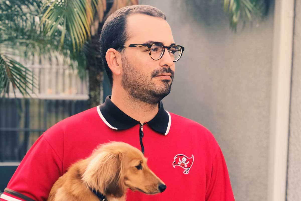 Joey Nelson in red Bucs polo while holding his dog, Ace