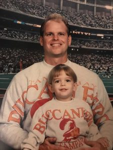 Young Joey and his father pose for a photo while wearing matching Bucs sweaters