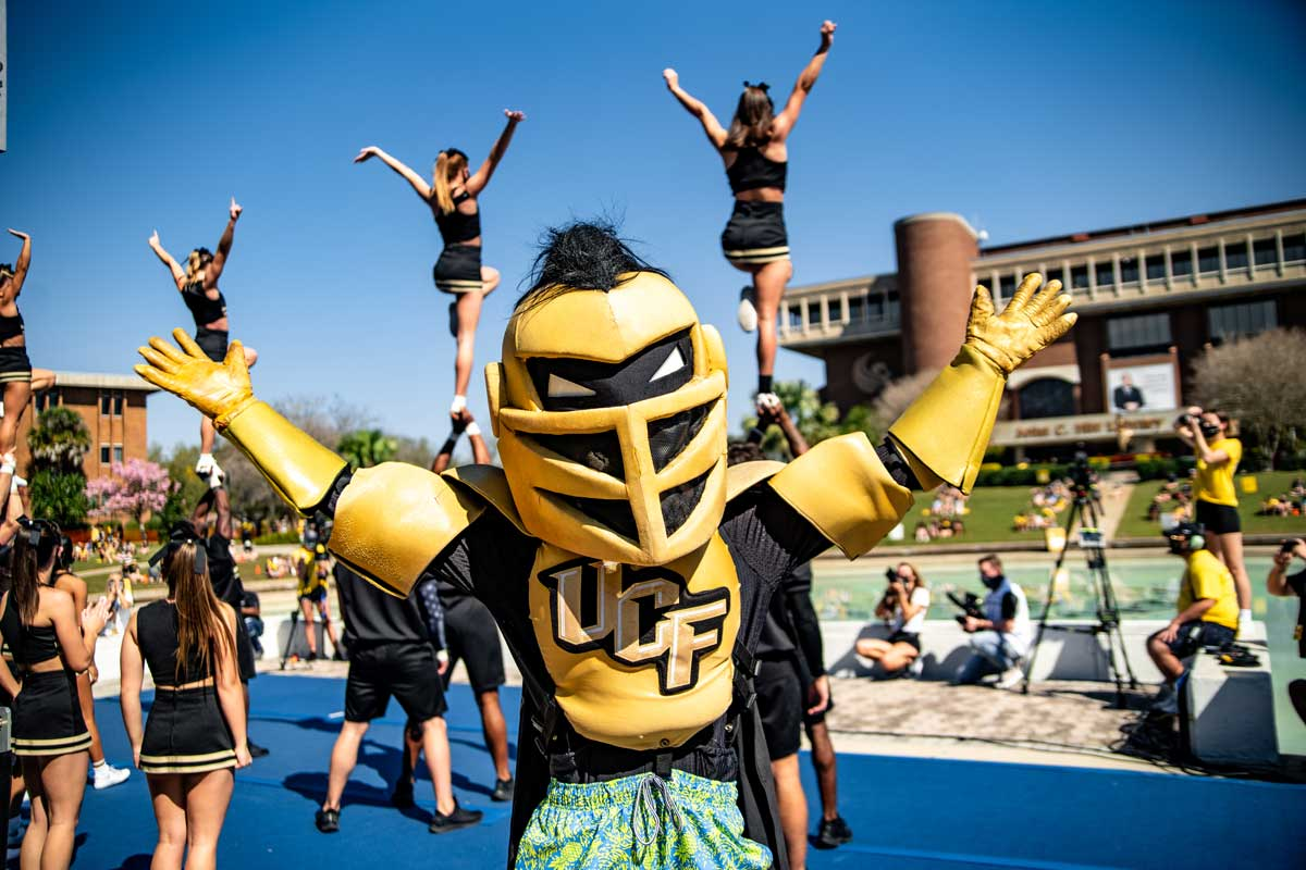 Knightro poses with arms stretched out in front of the cheerleaders stunting