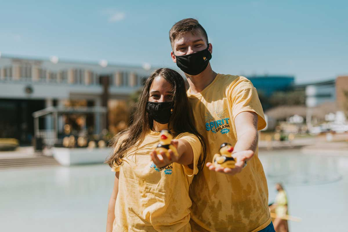 Two students hold out their spirit splash ducks