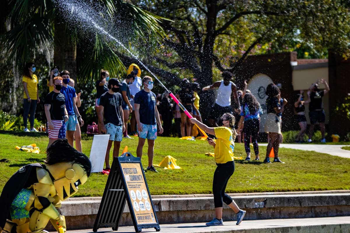 Woman sprays water soaker at crowd of students