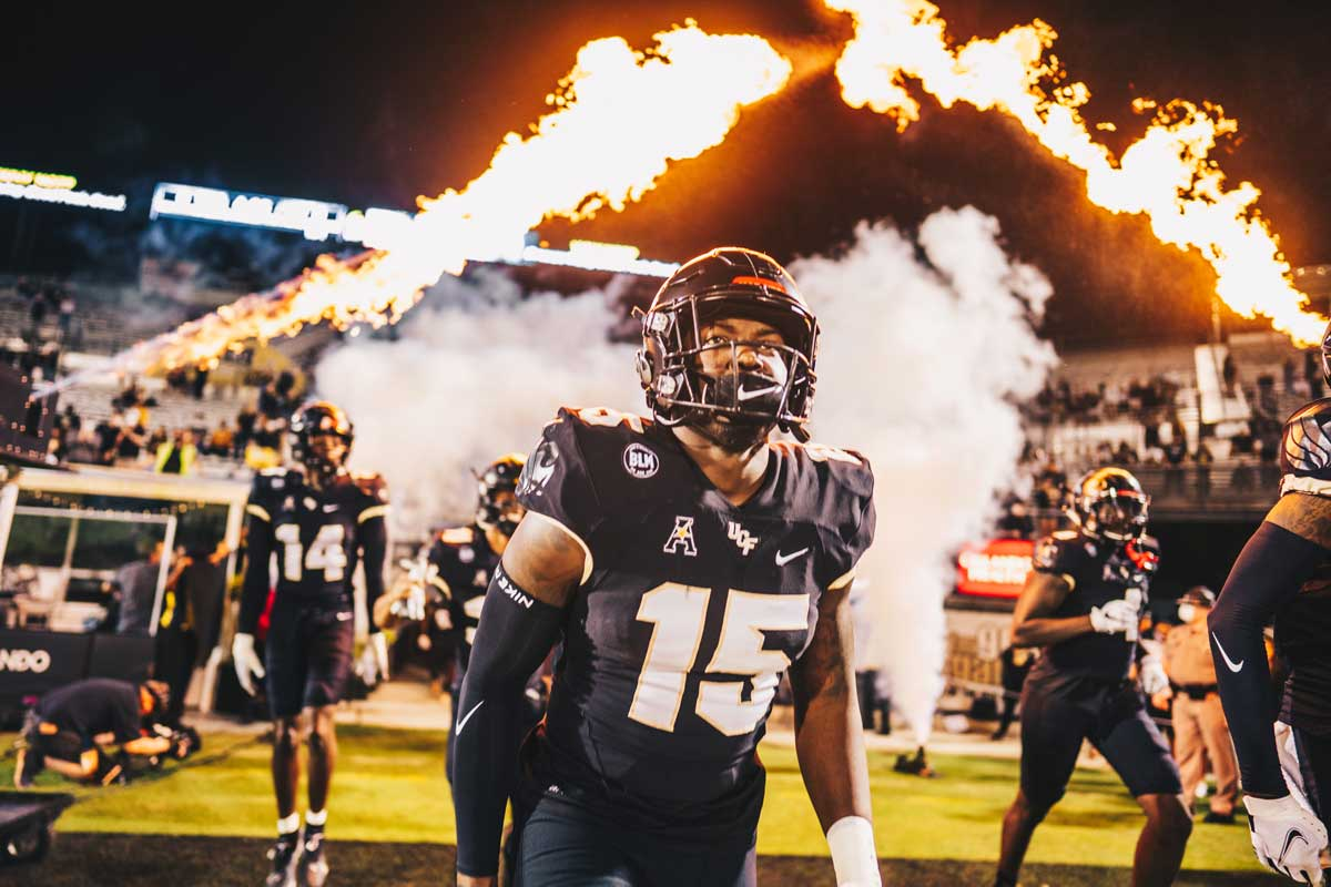 UCF football player wearing #15 jersey runs onto the field with pyrotechnics shooting behind him.