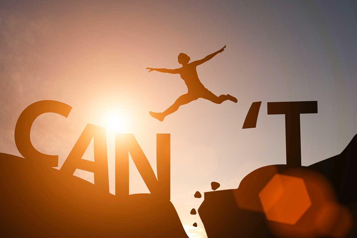 Silhouette of a person soaring from one boulder to the next, jumping over the word Can't