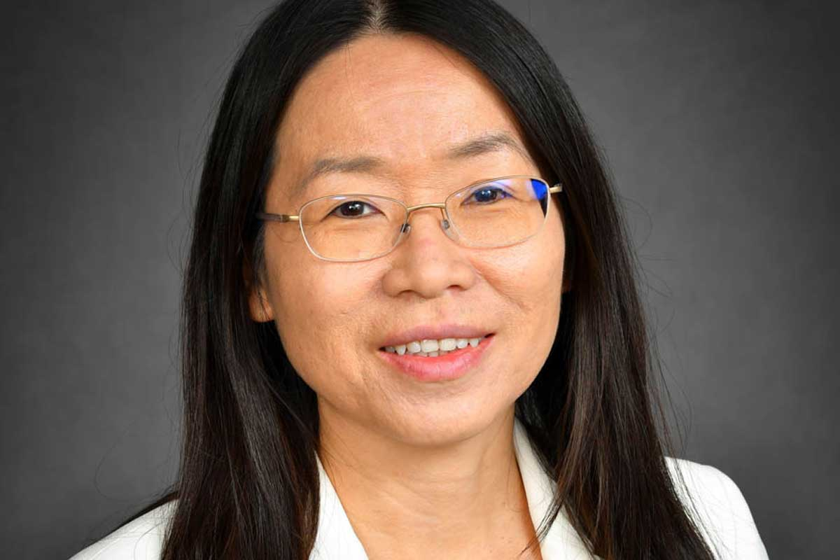 Headshot of Asian woman with glasses and white blazer