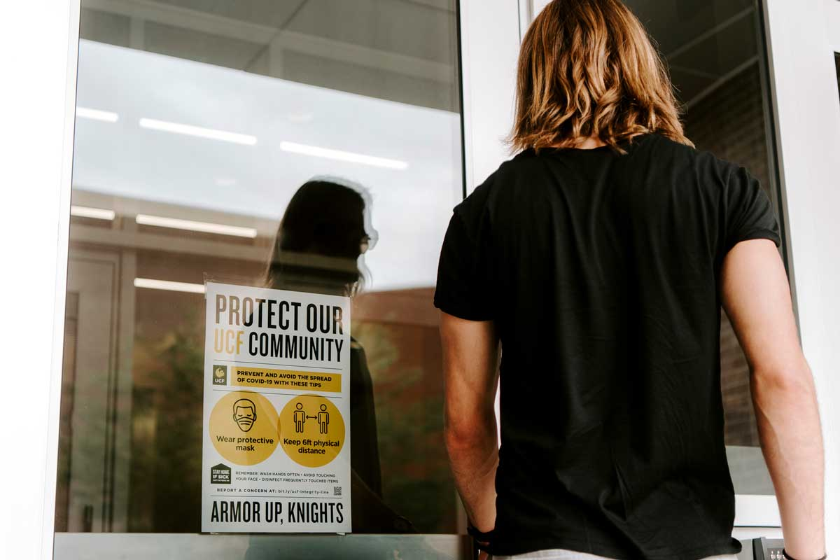 "Person with shoulder length hair prepares to enter building with a sign on glass door that reads ""protect our community"""