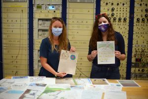 Allison Smith and Anna McGilvray with Arecibo Observatory hold letters of support from Orlando-area schoolchildren
