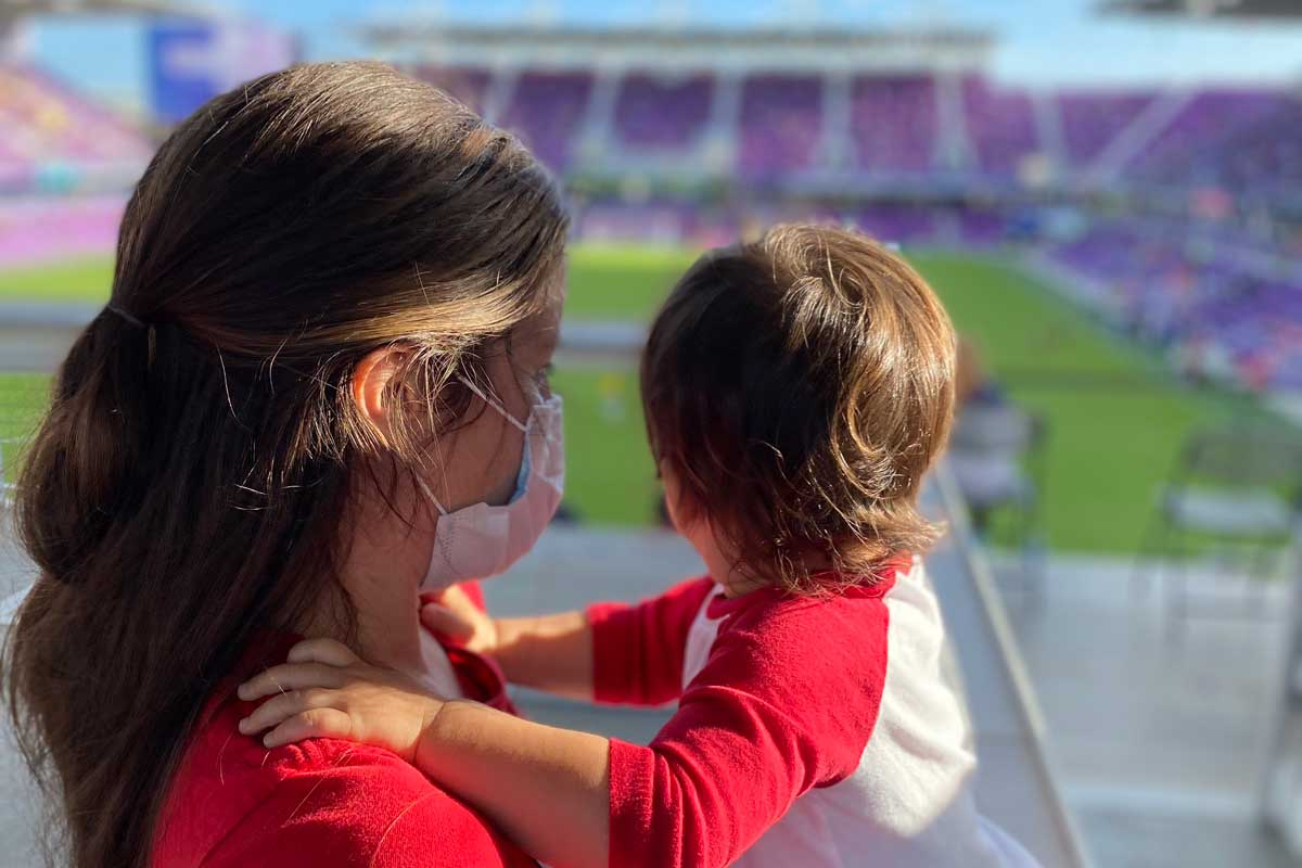 Profile shot of a mother holding her toddler son at a stadium