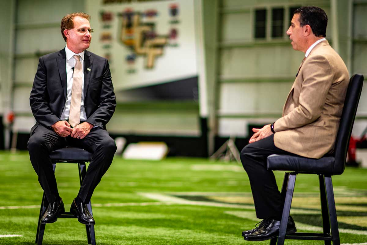 Marc Daniels and Gus Malzahn sit to have a conversation inside the Indoor football practice facility