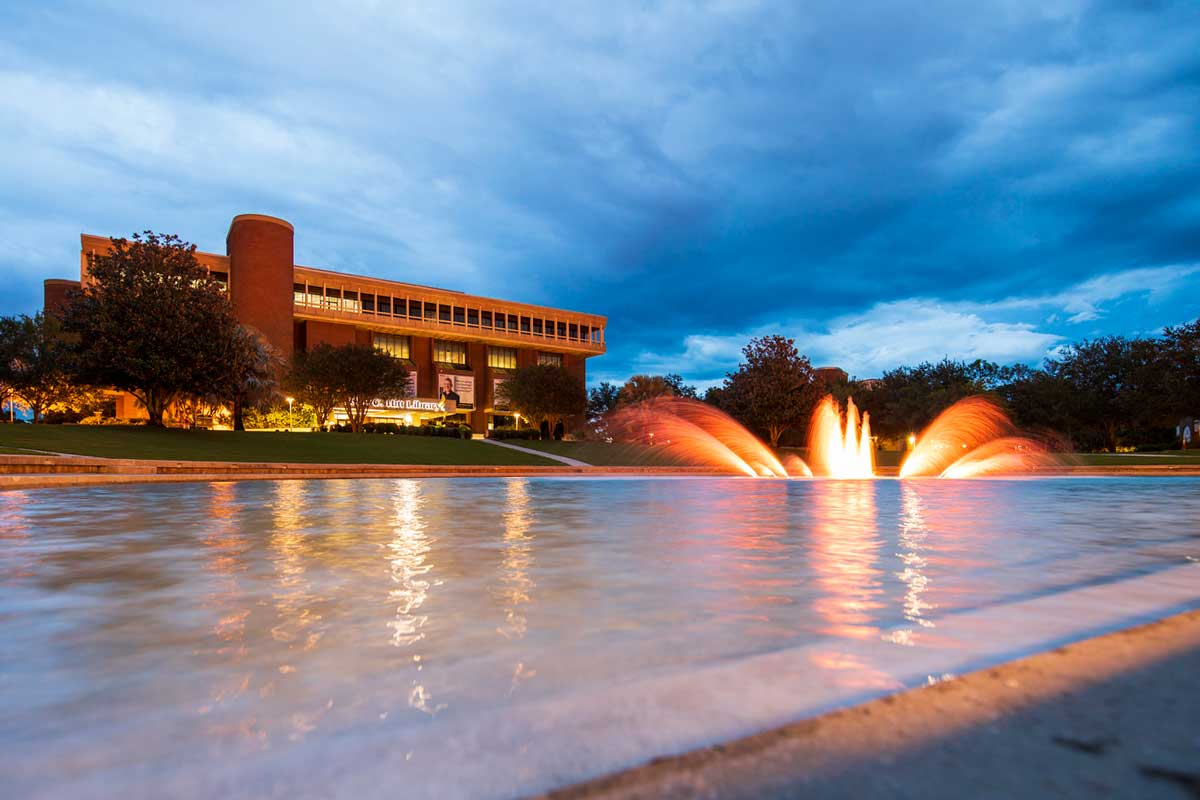 reflecting pond with fountain feature lit in orange
