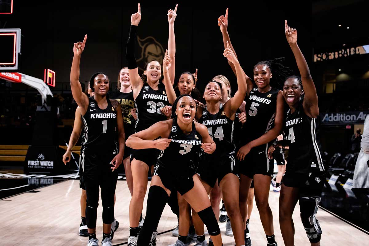 Women's Basketball team huddles in celebration, arms raised and smiling/yelling at camera