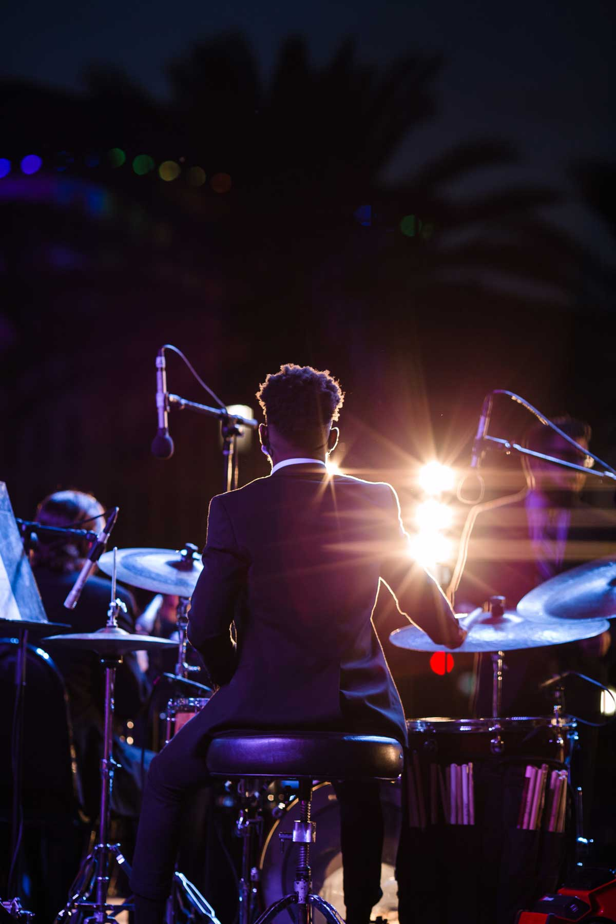 Photo of student seated at drums on stage at night, view from behind