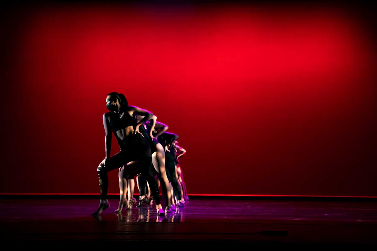Dancers form a stacked line on stage with a red backdrop