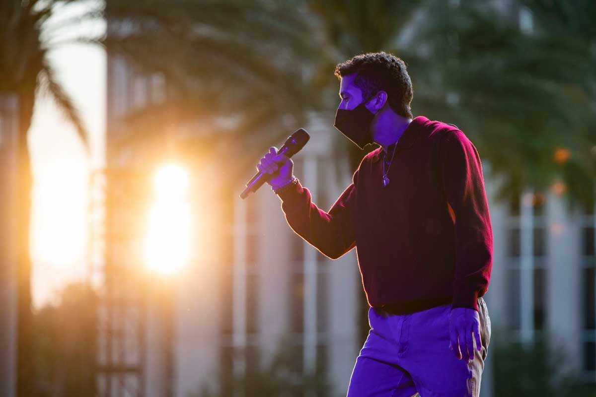 Man sings into a microphone while wearing a mask as the sun sets behind a building in the distance