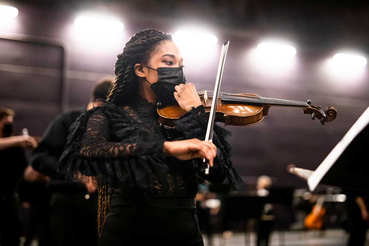 Black woman raises bow to violin