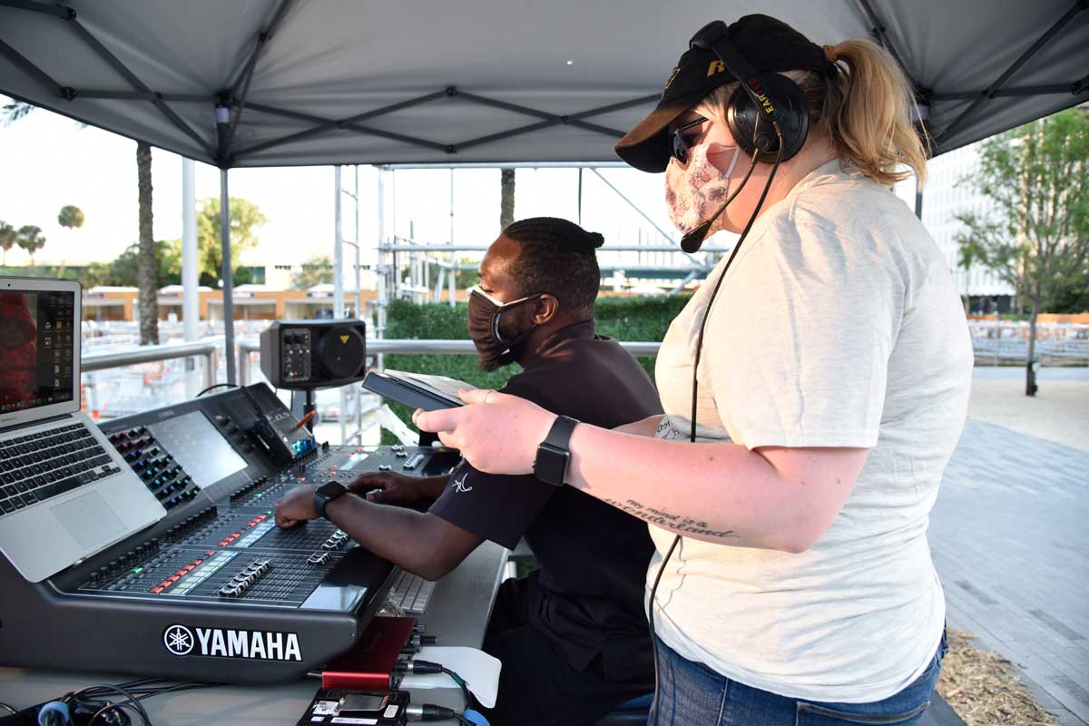 Woman with headset stands next to man seated at sound board under a tent