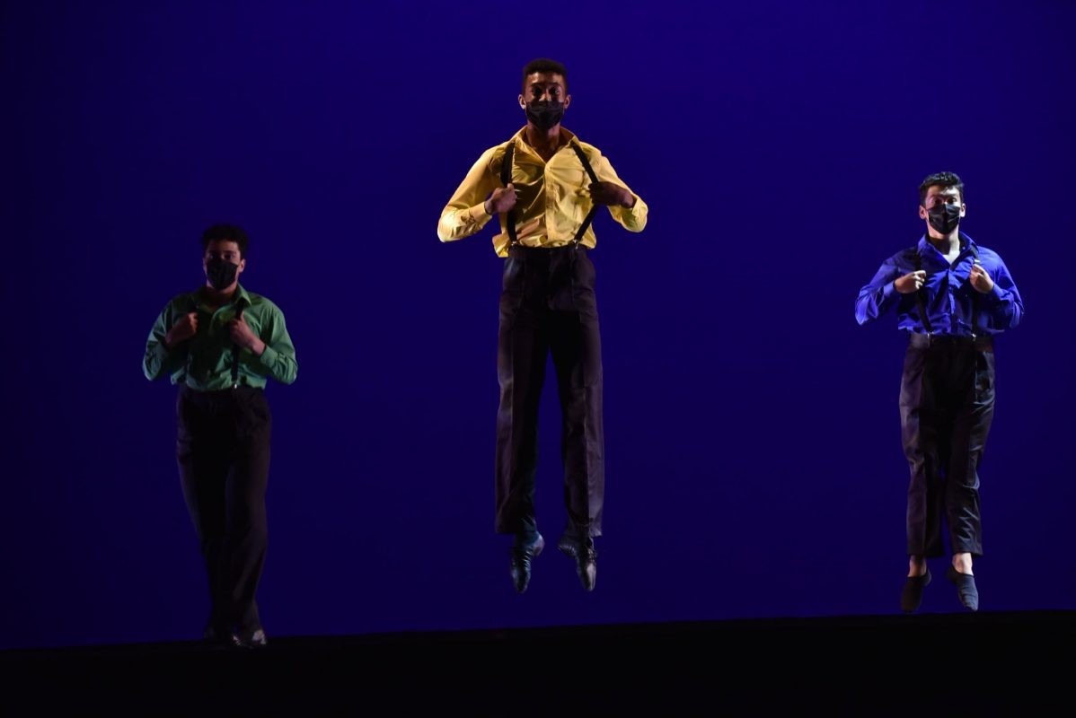 Three dancers wearing dress shirts and pants with suspendersjump on stage