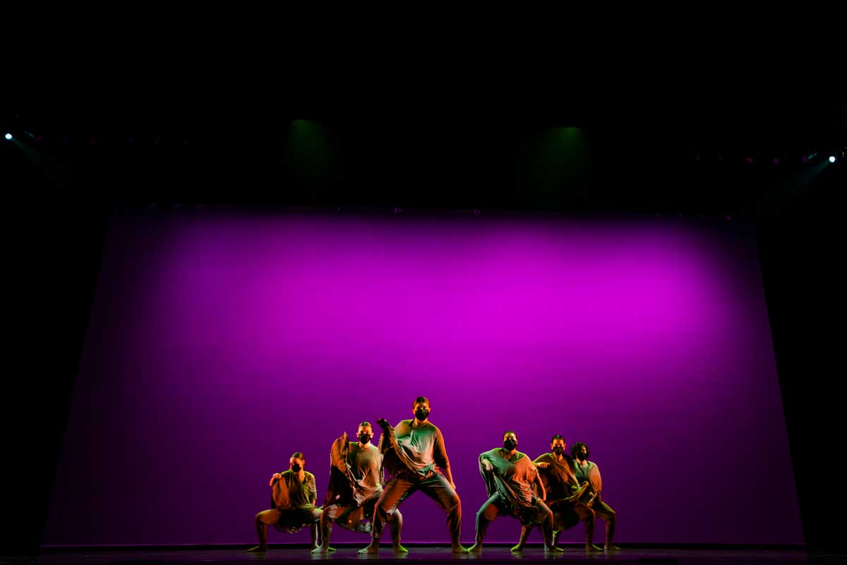 Dancers form V on stage with purple background