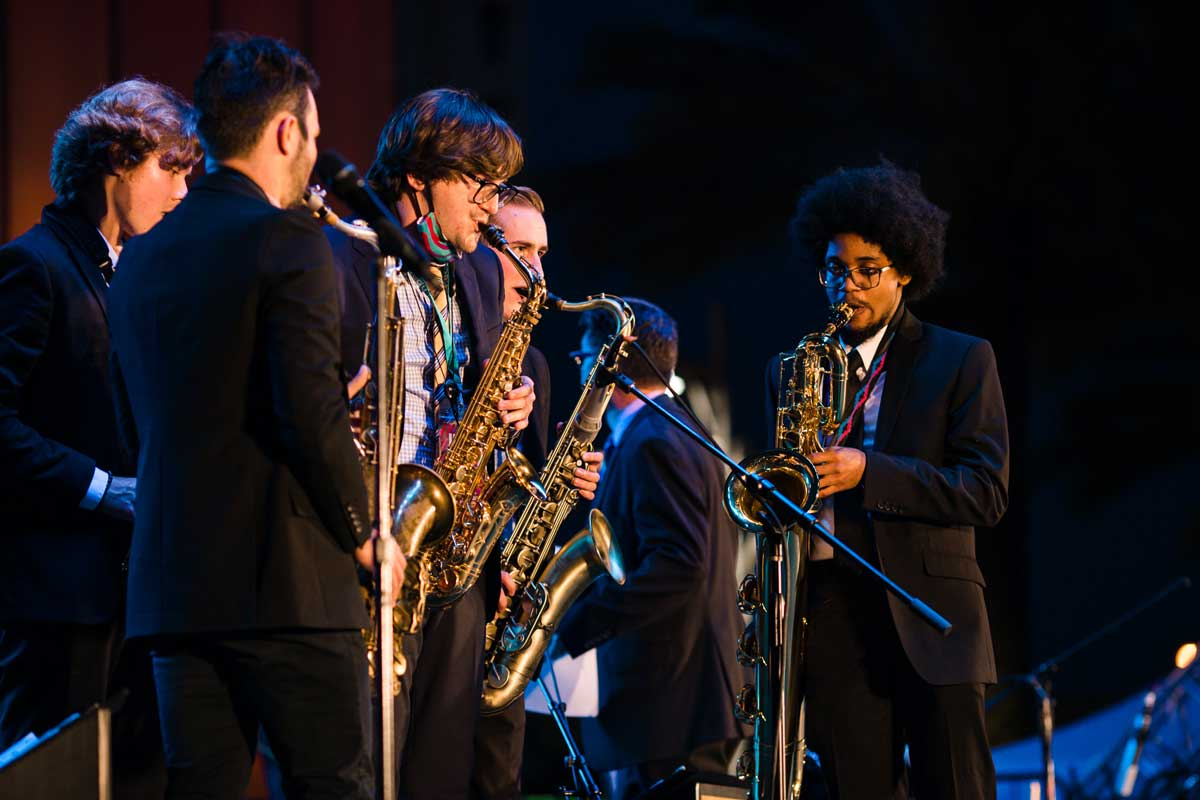 Group of saxophonists perform on stage