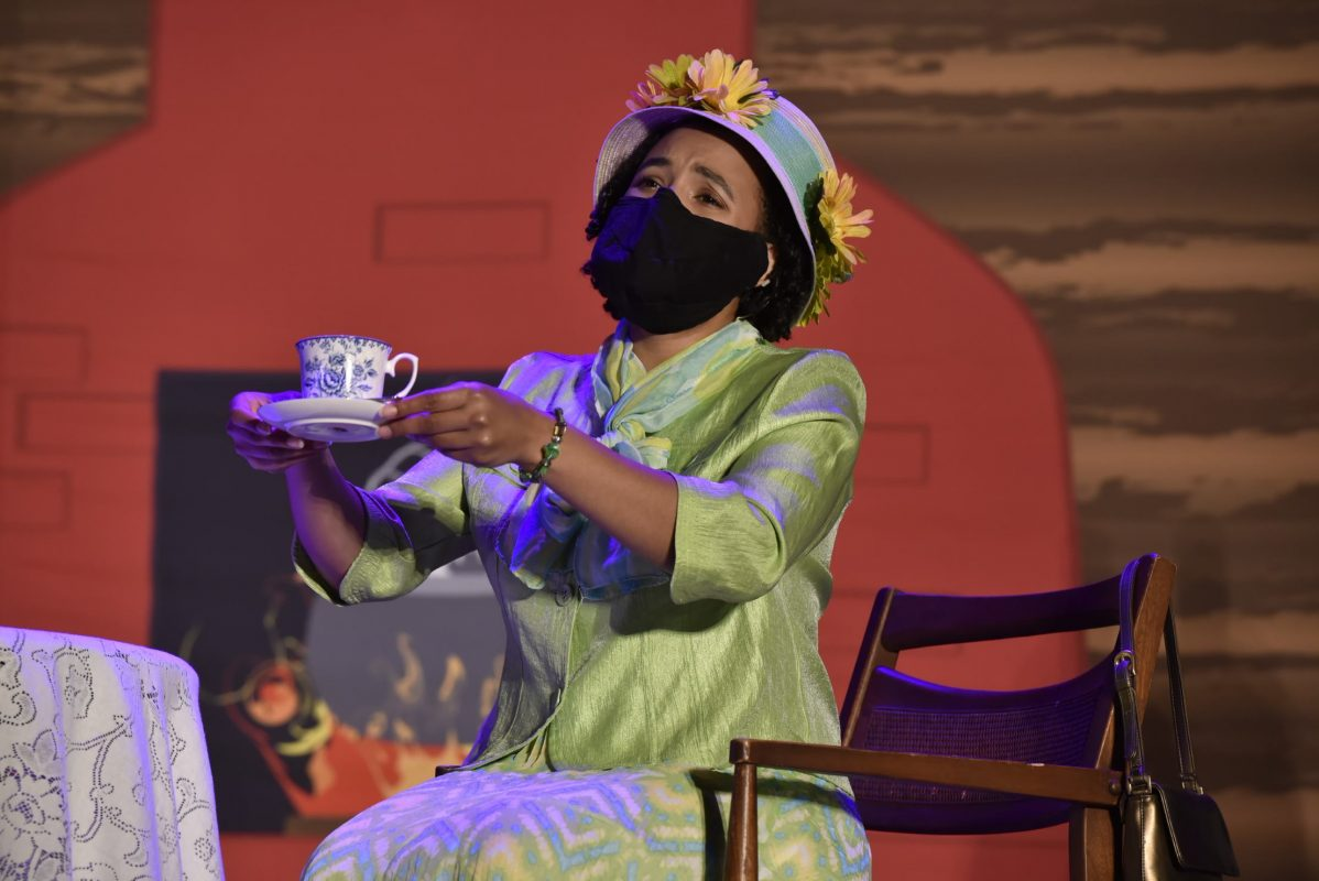 Black woman in costume lift up tea cup and saucer while sitting in a wooden chair on stage