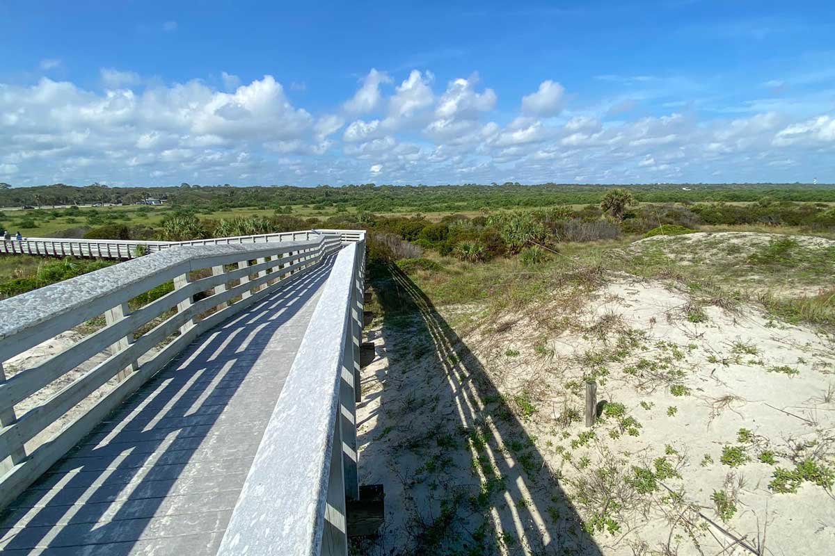 white boardwalk in between sand dunes leads to beach on sunny day