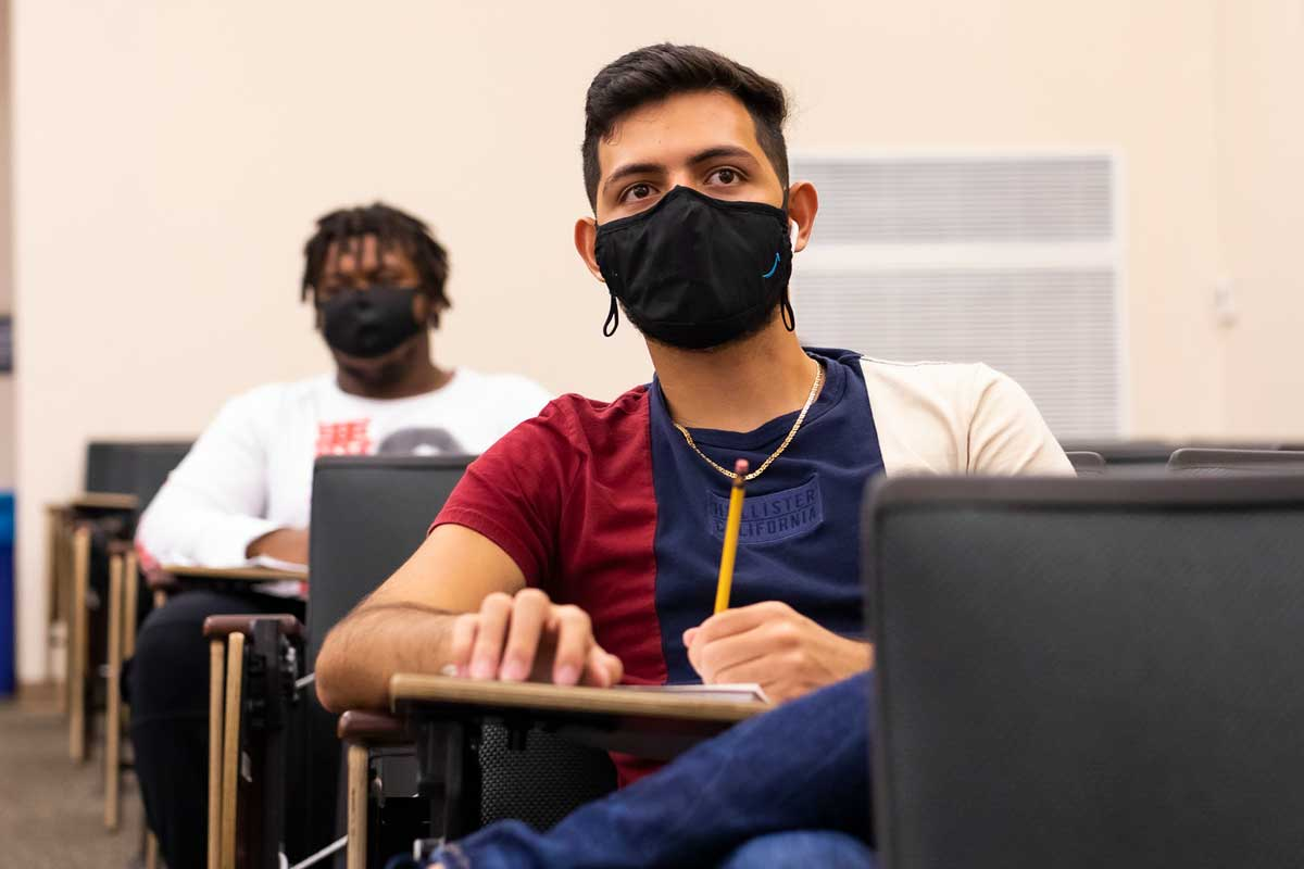 Two students sit at classroom desks while wearing black masks