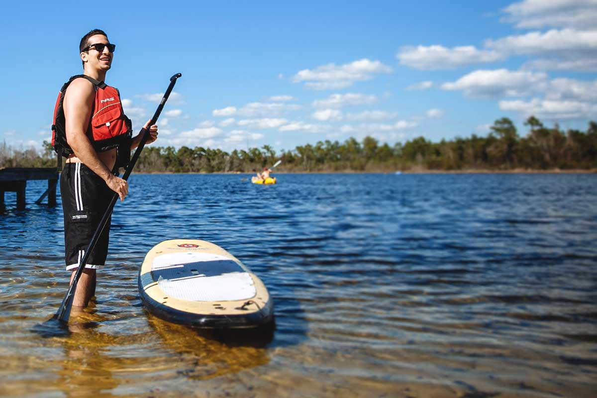 Man in life jacket holds paddle standing next to paddleboard in water