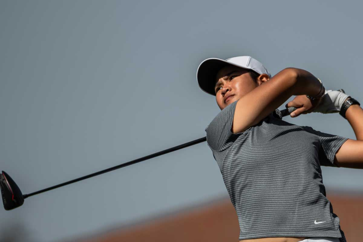 Women's golf player holds club after swing