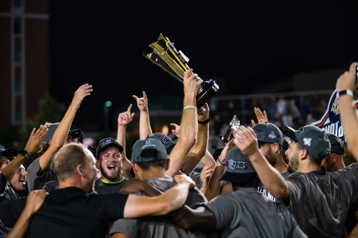 men's soccer team huddles with trophy raised overhead