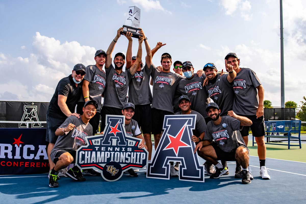 men's tennis team holds AAC Champion signs and trophy on court
