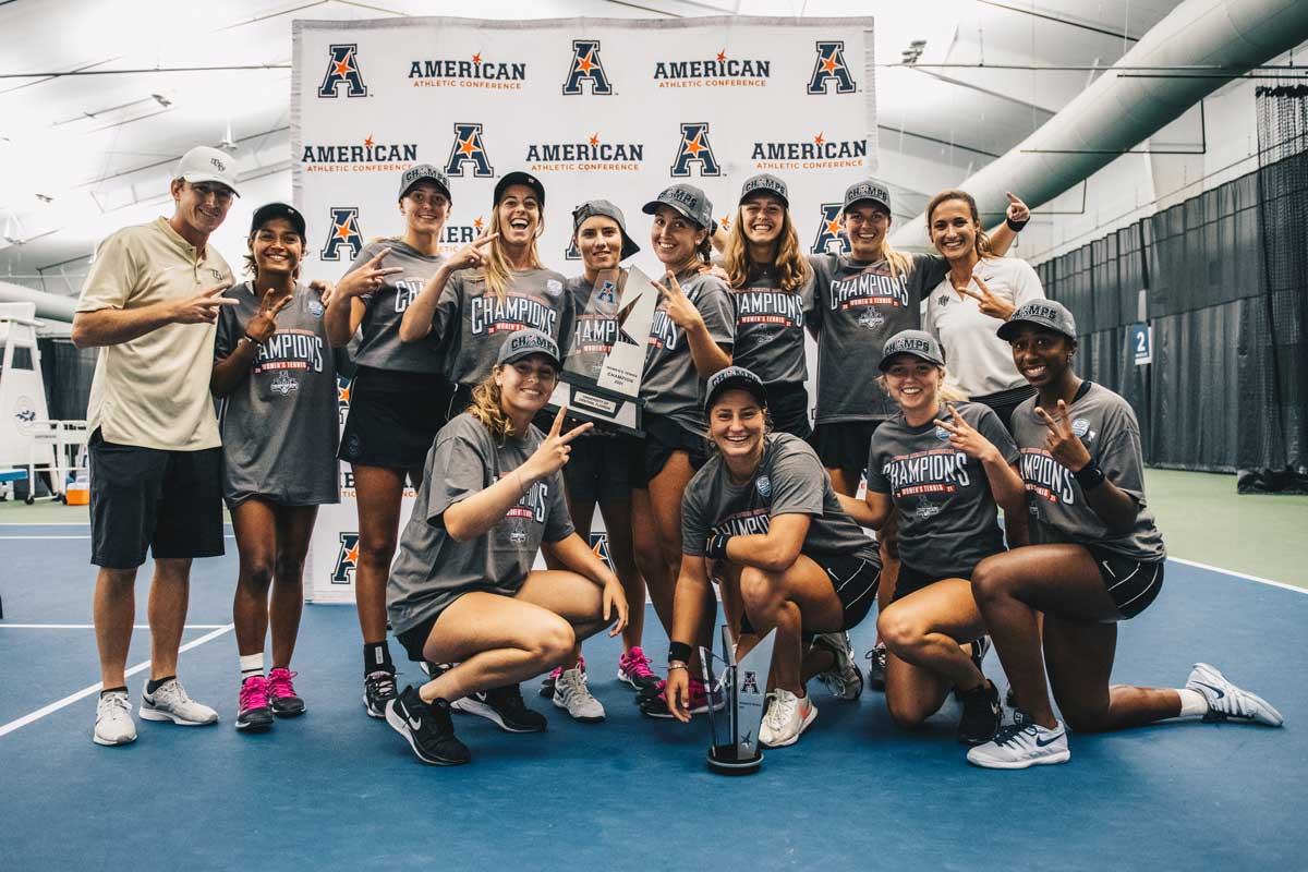 UCF women's tennis team holds two trophies on court
