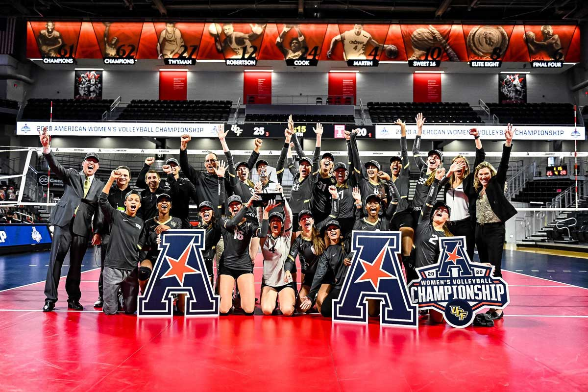 volleyball team poses on court with AAC trophy
