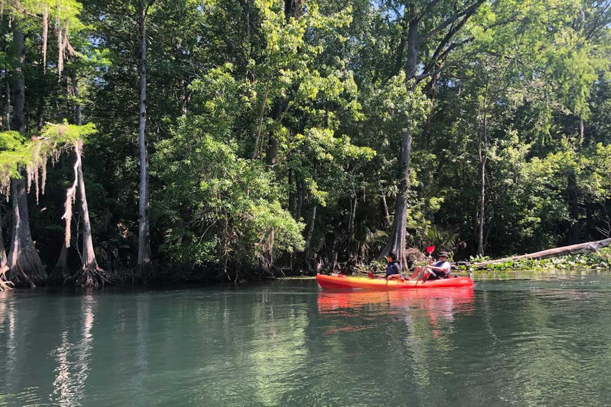 Kayakers in a red kayak launch into Weikva River