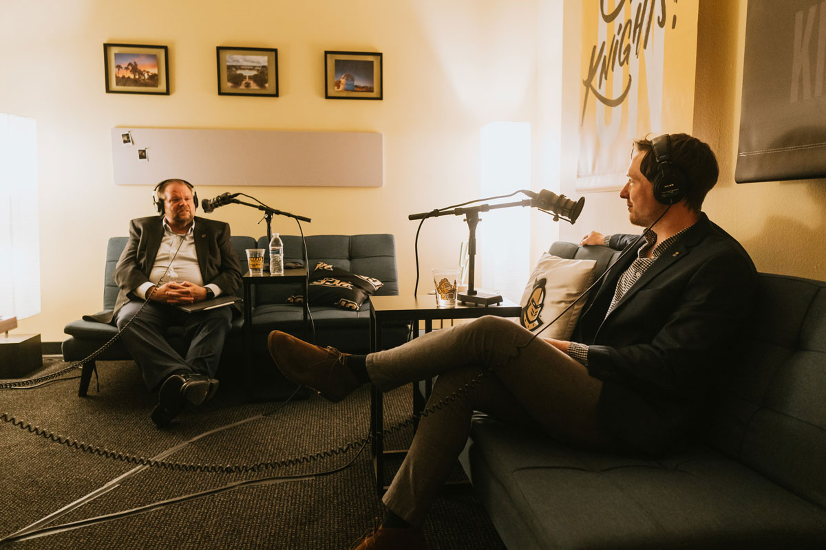 President Alexander Cartwright and host Alex Cumming sit on couches during recording session