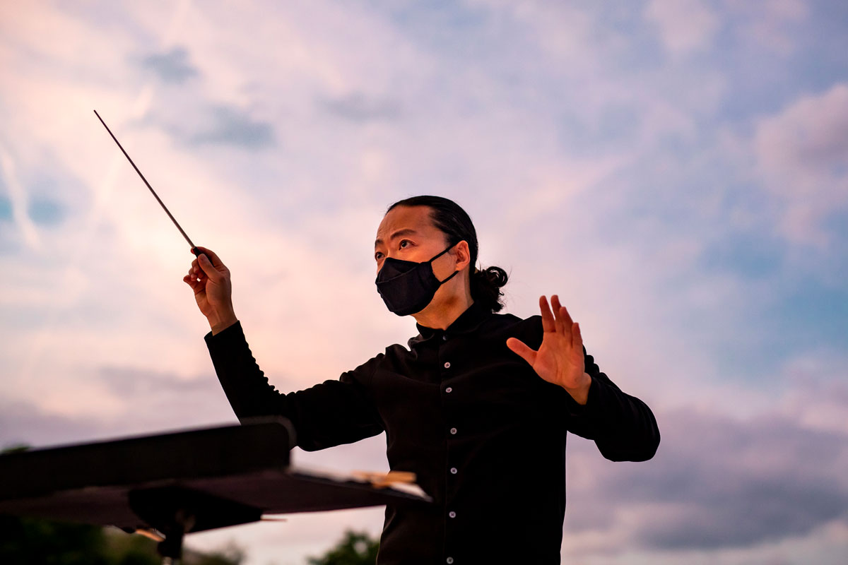 Chung Park conducts orchestra during sunset