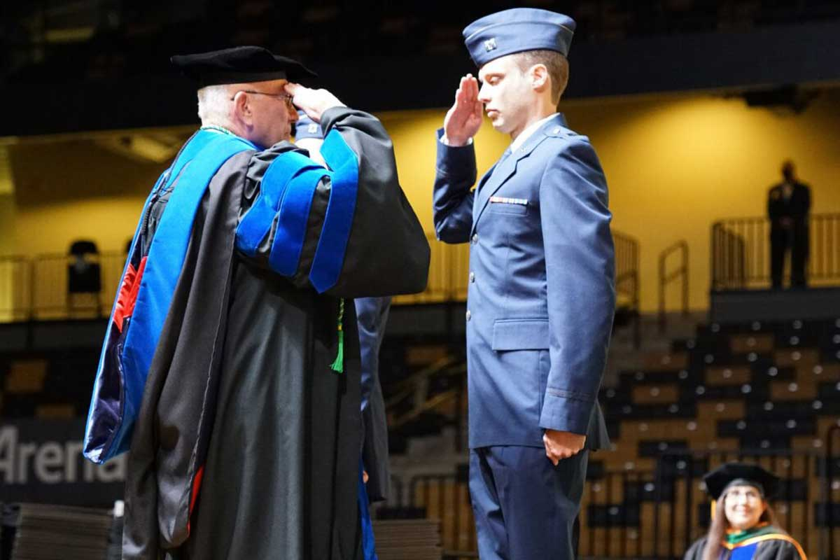 Richard Peppler salutes student in blue military uniform on stage during commencement ceremony