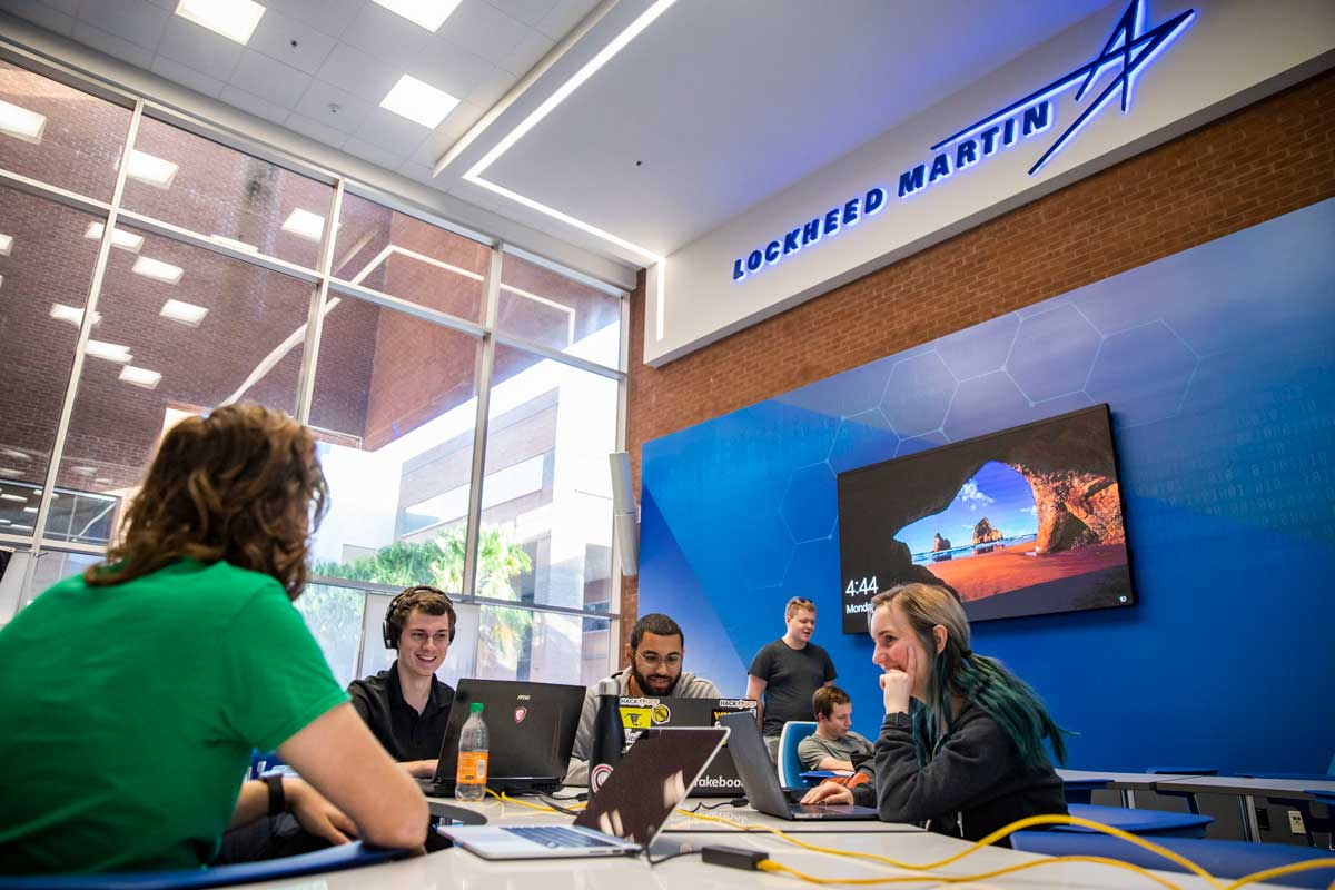 Four students sit at a desk with computers at Lockheed Martin Cyber Innovation Lab