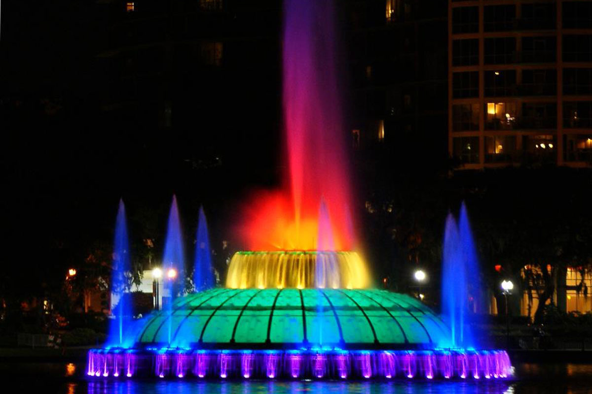 Lake Eola lit up in rainbow colors at night