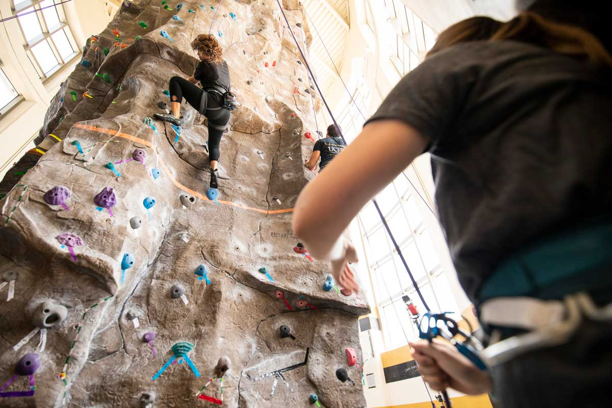 spotter stands on the ground and watches two climbers on rock wall indoors